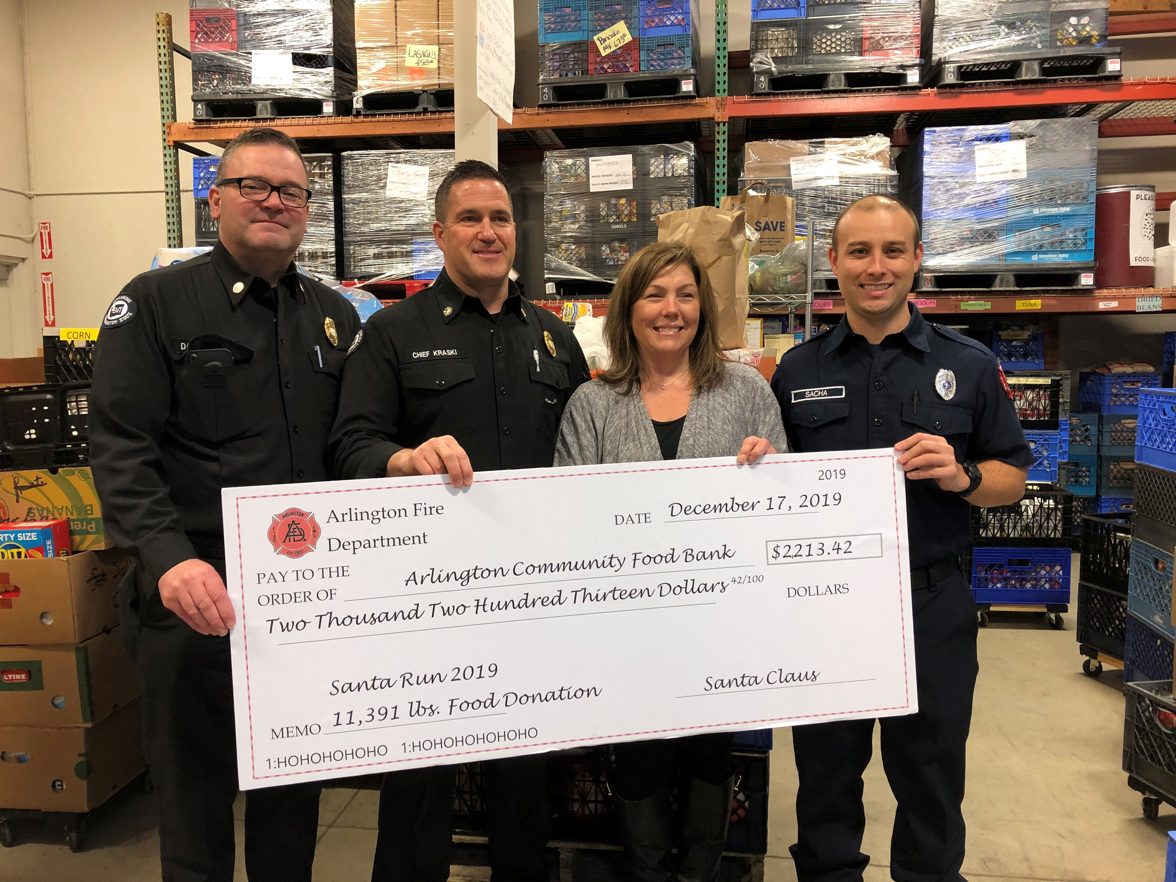 Arlington Fire Department staff present large check to Arlington Community Food Bank for 2019 Santa